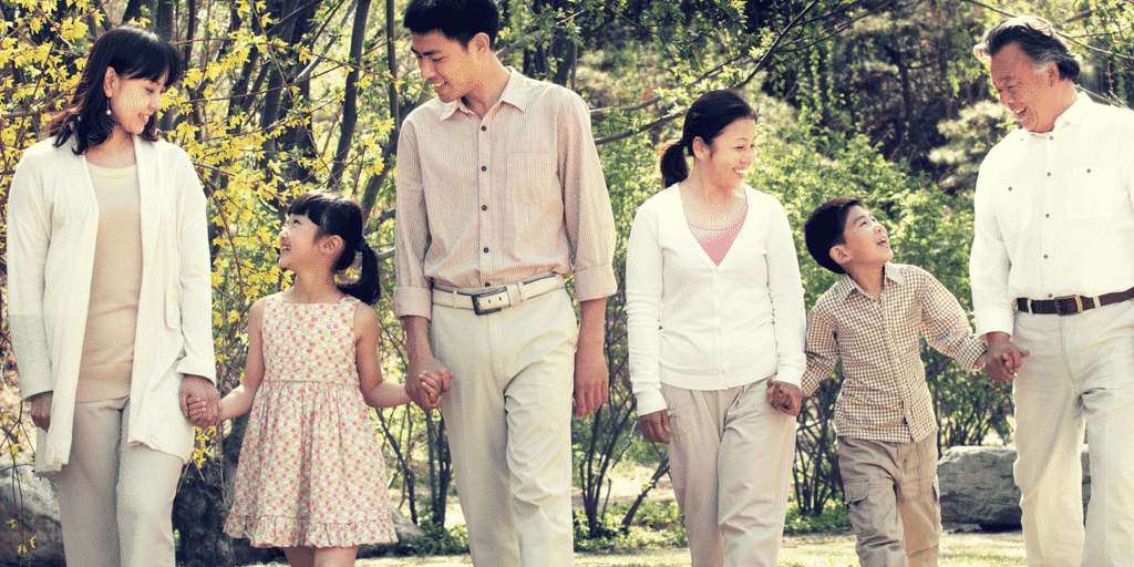 mom, dad, children and grandparents walking hand in hand in post about parenting as a team