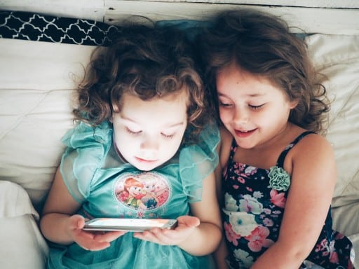 Two girls playing on a mobile phone