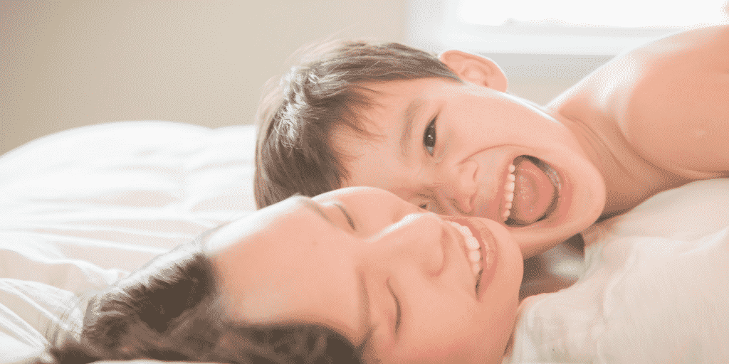 boy with mum laughing in bed in post about children anxious about change