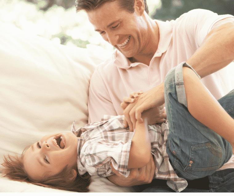 Dad tickling son