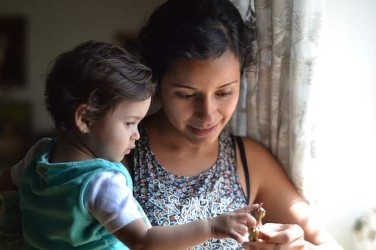 Mother and young boy looking at a toy